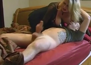 Mother caressing son's cock in bed